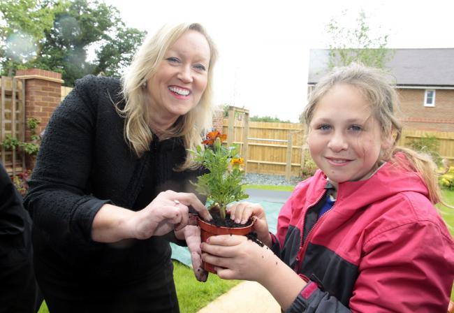Bewley Homes , Sales and Marketing Director, Elaine Stratford with pupils from Bramley C of E Primary School,potting their own plants, during their visit to  Centenary Fields, Bramley, Hampshire.