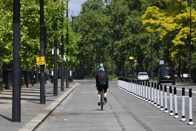 A cyclist uses a pop-up cycle lane in Park Lane, London. Bollards have been added to the road to create segregation between cyclists and other road users as part of mayor Sadiq Khan's London Streetspace programme. PA Photo. Picture date: Thursday May