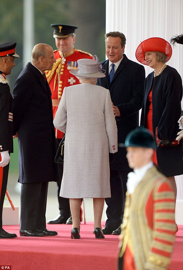 Theresa May, with then-PM David Cameron, meets the Queen and is wearing one of Liz Felix's creations