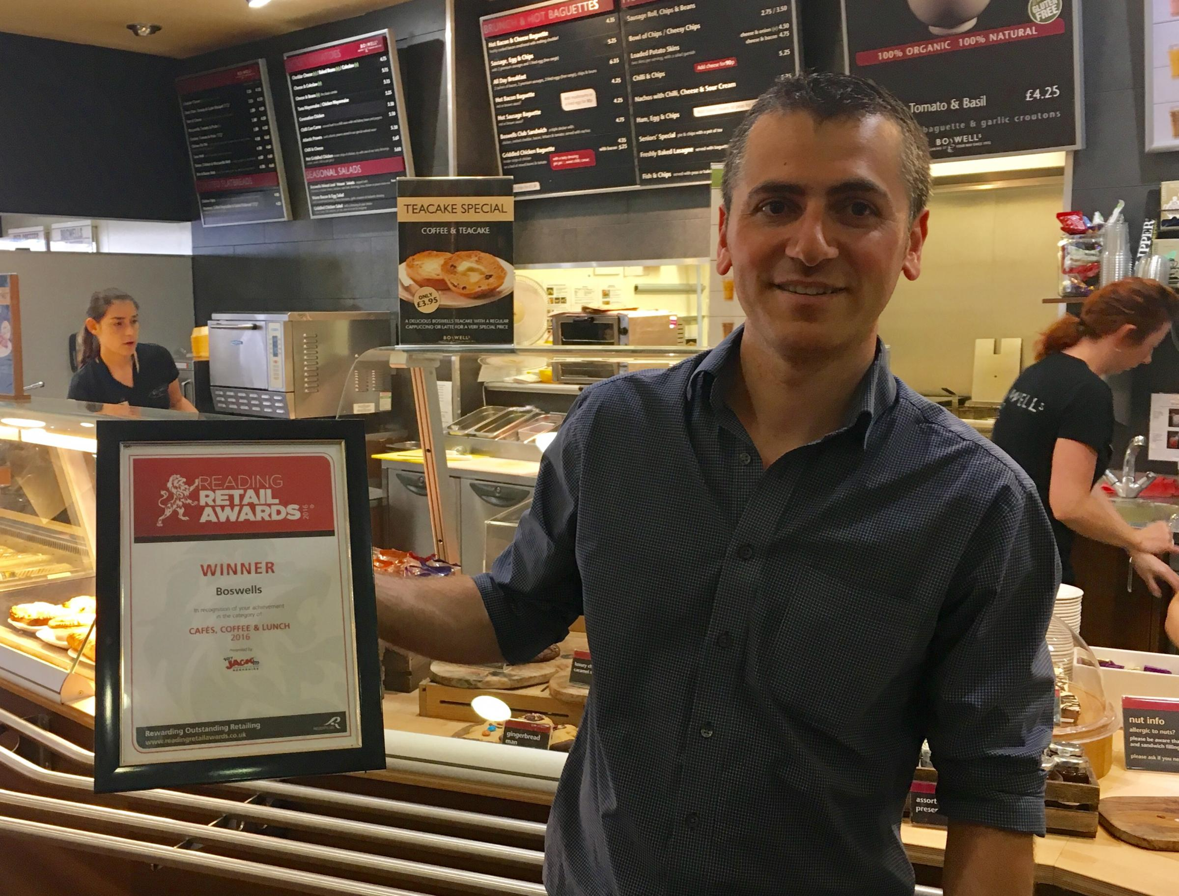 Adam Agirbas, manager of Boswells, proudly holds his award as the leader of the best cafe in Reading