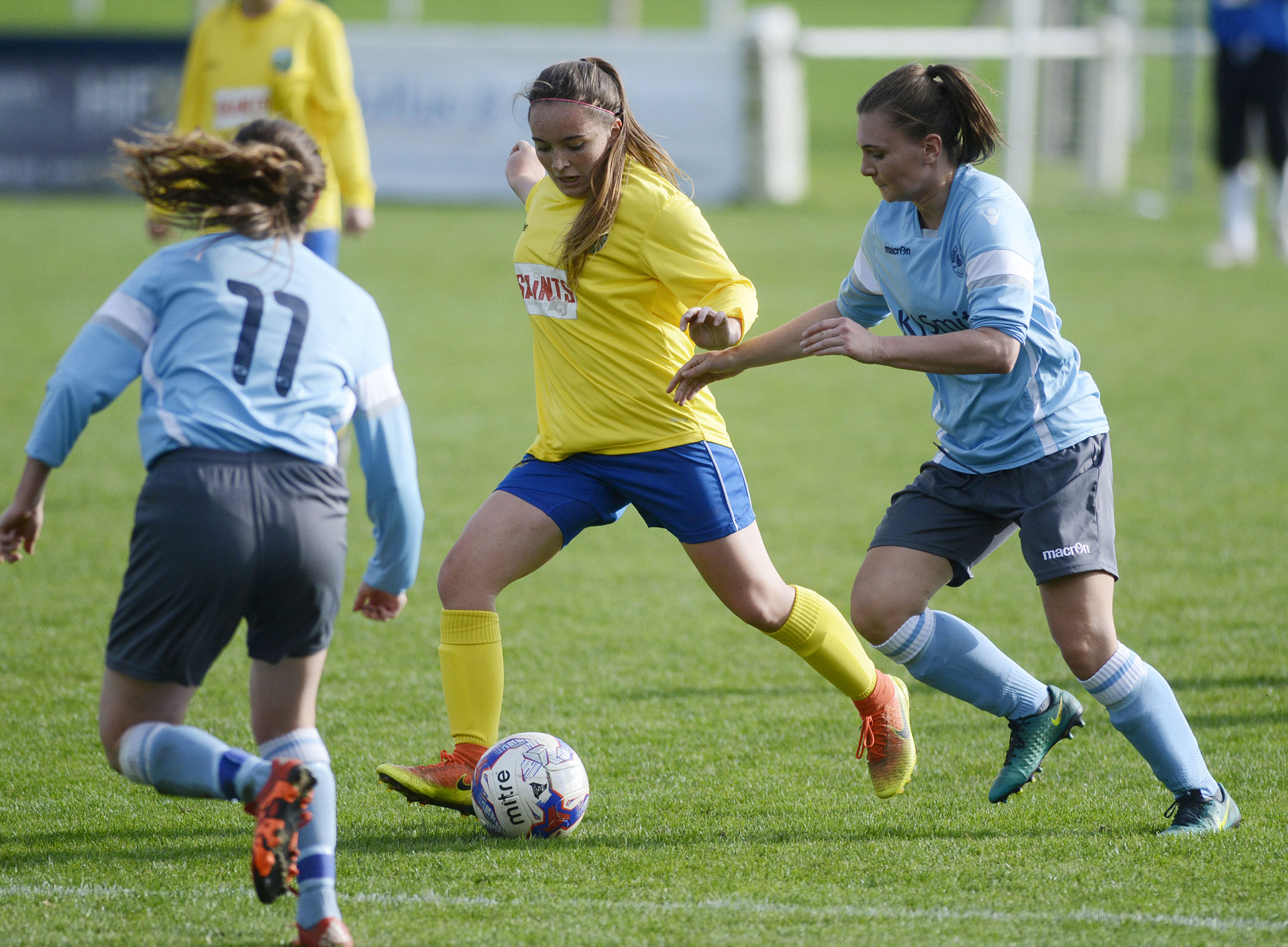 Woodley United Ladies (blue) try to win the ball back from Ascot United
