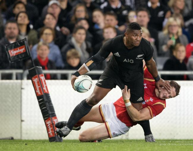 New Zealand All Black Waisake Naholo, left, fends off a Welsh defender during their rugby union test match in Auckland, New Zealand, Saturday, June 11, 2016. (Greg Bowker/New Zealand Herald via AP) NEW ZEALAND OUT, AUSTRALIA OUT.